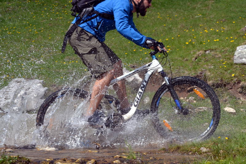 Mountain biking through creek on Durmitor - meanderbug