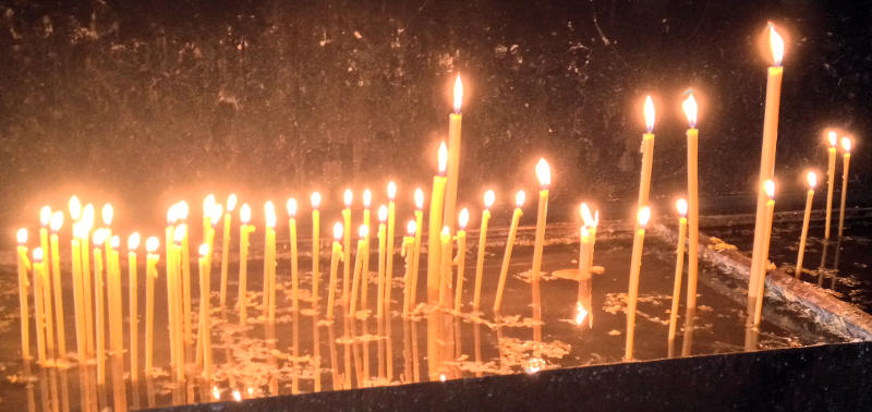 Lit candles at Ostrog Monastery - meanderbug