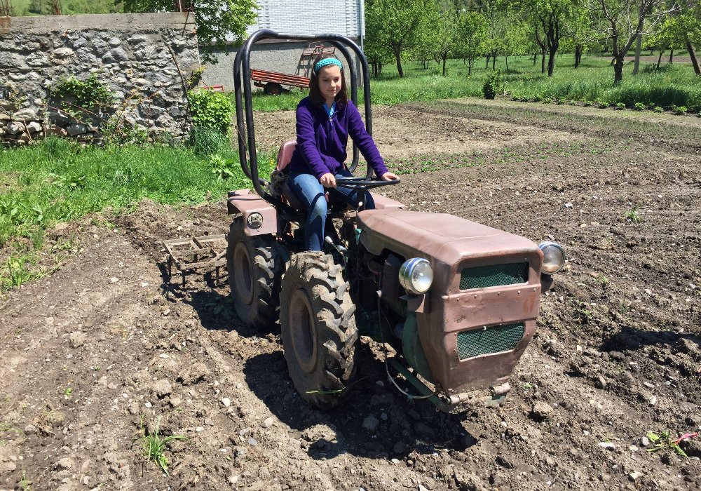 Village life opens possibilities for kids like driving a tractor
