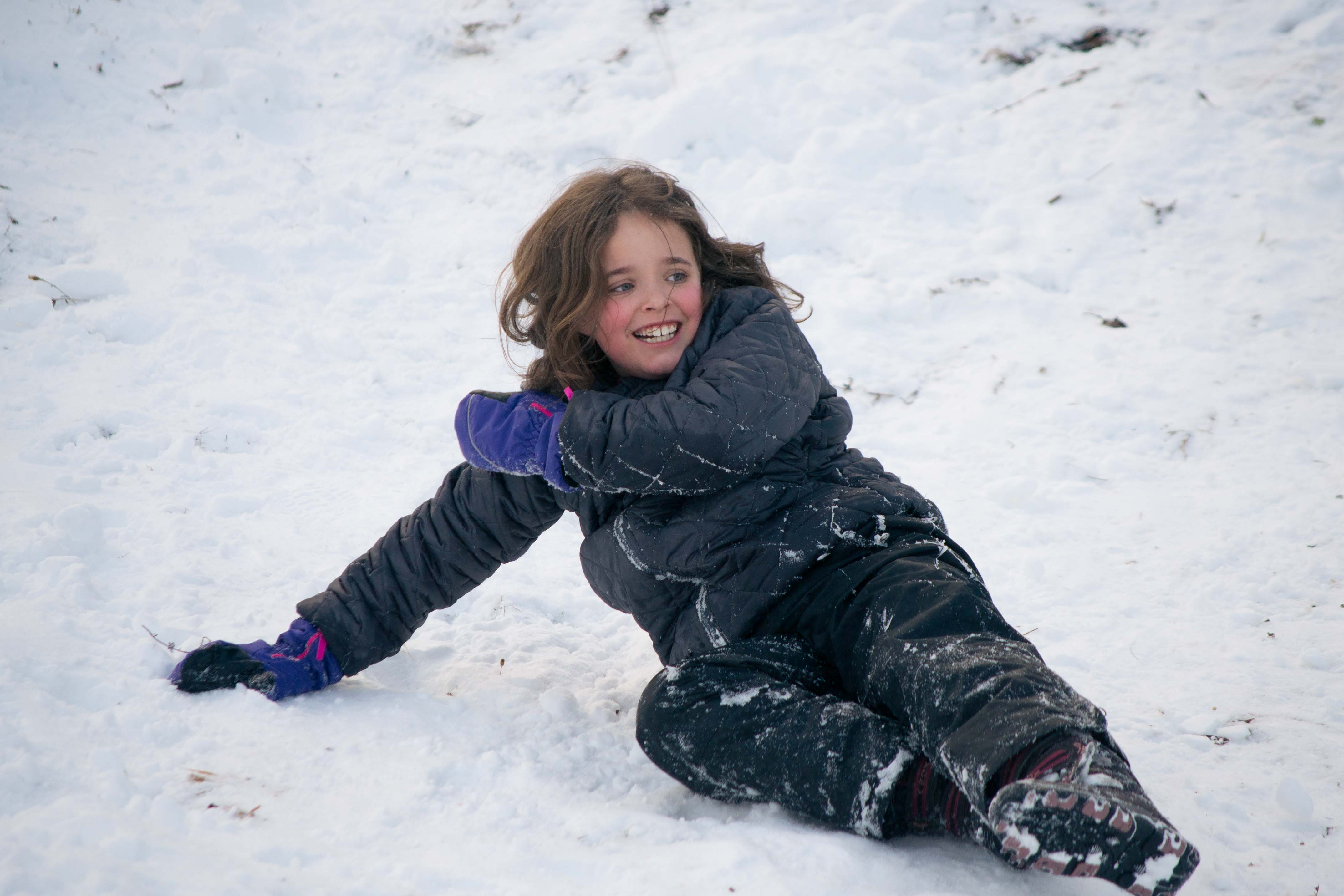 A young girl's winter sledding smile